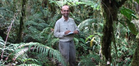 Yadvinder in the rainforest with a note book and pen